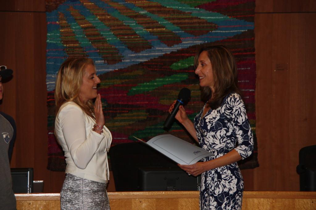 School Board President Gina Daleiden swears in Rochelle Swanson for a second term.