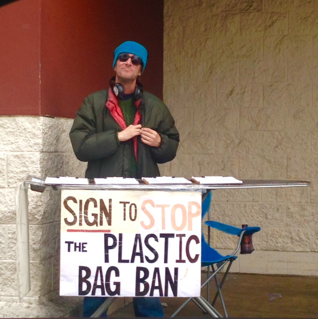 A signature gatherer outside a local big box collects signatures in November 2014