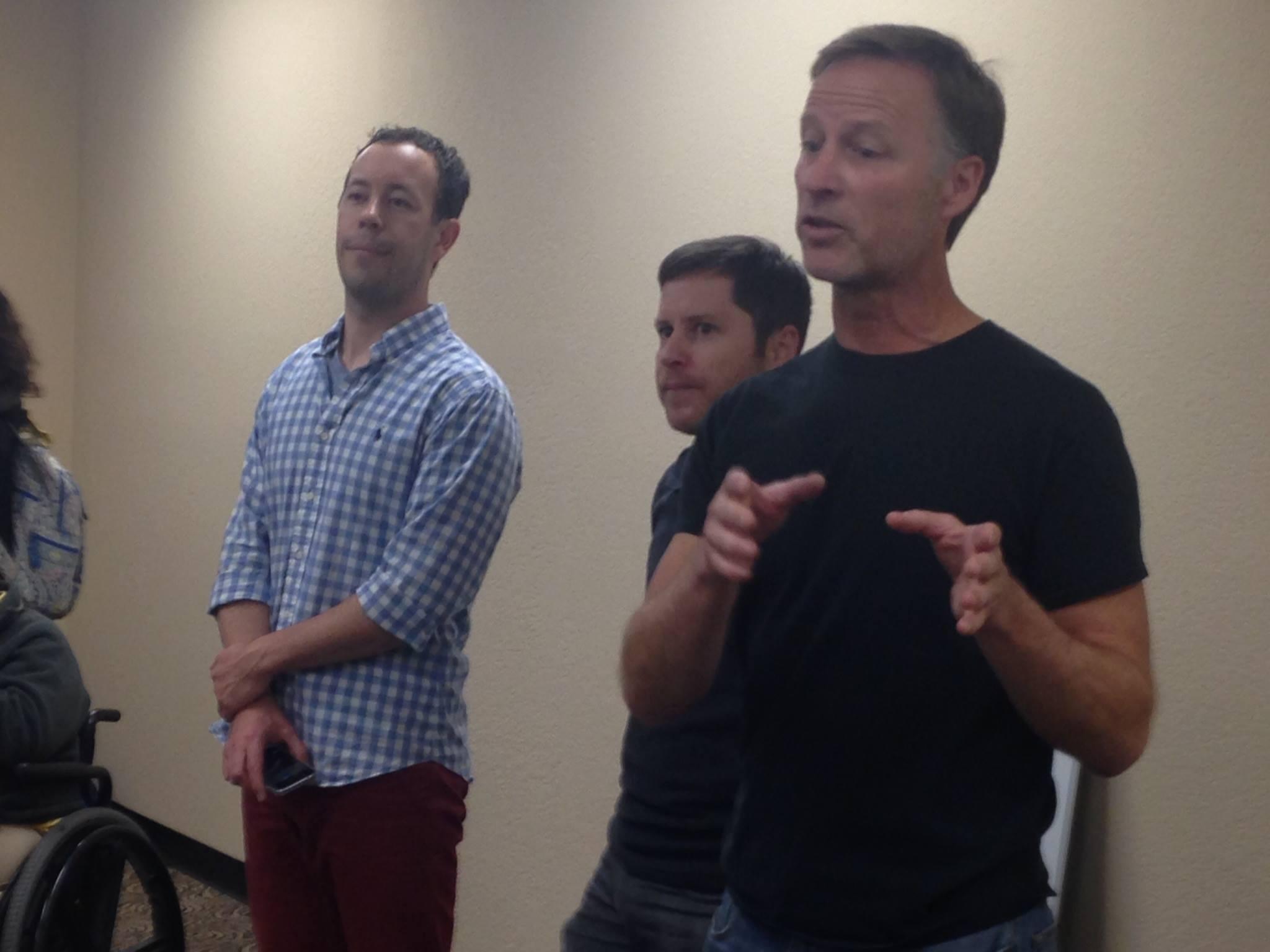 Matt Miller (left) listens as Michael Bisch (far) right speaks with Bill Habicht (center)