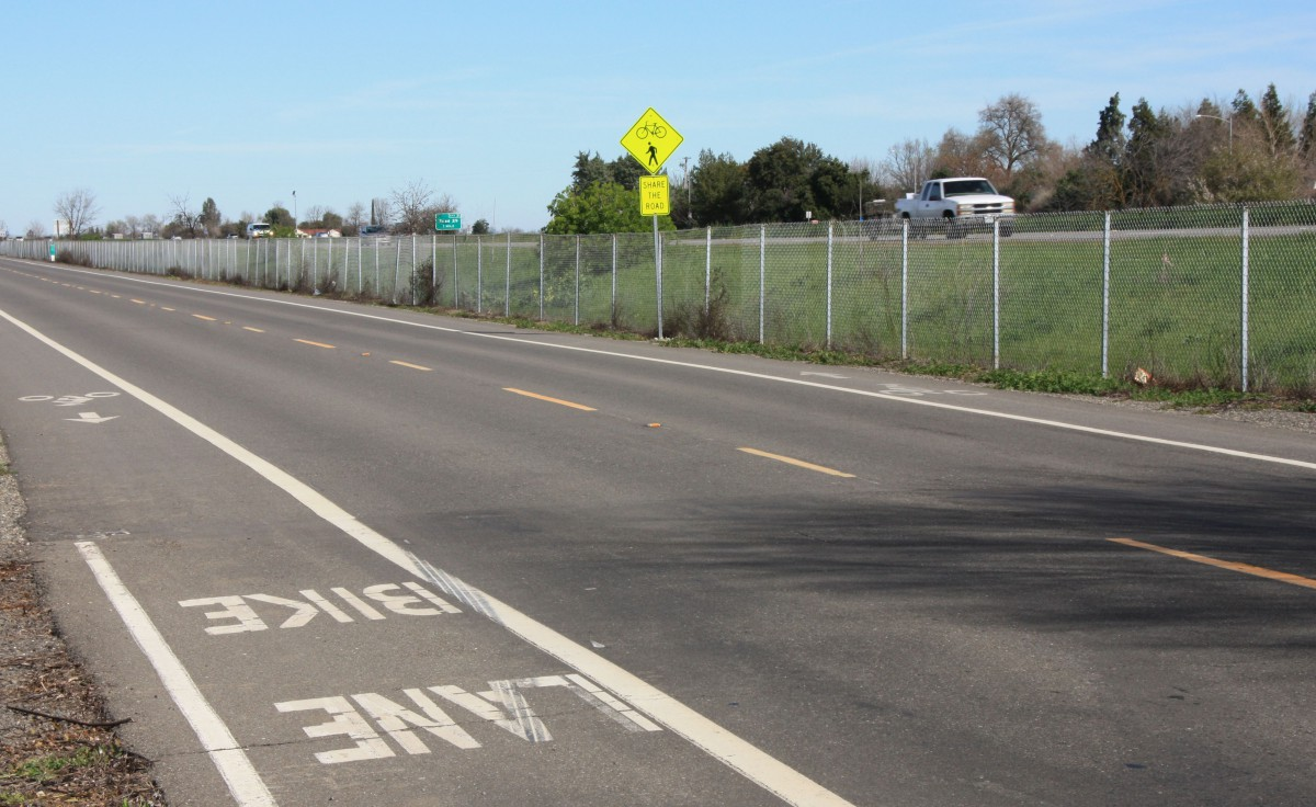 Road 99D is a narrow two-lane road with bike lanes on both sides and the freeway to the east.