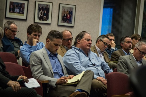 Dan Ramos listens to council comments surrounded by his team