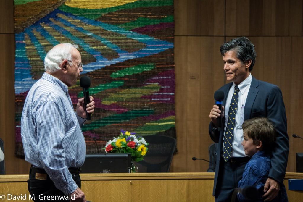 Brett Lee holds his son Jasper as Richard Livingston reads him the oath of office
