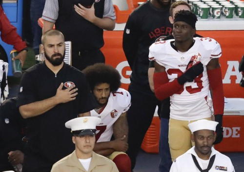 Colin Kaepernick (c.) kneels during the national anthem before the team's NFL preseason football game against the San Diego Chargers. (Chris Carlson/AP)